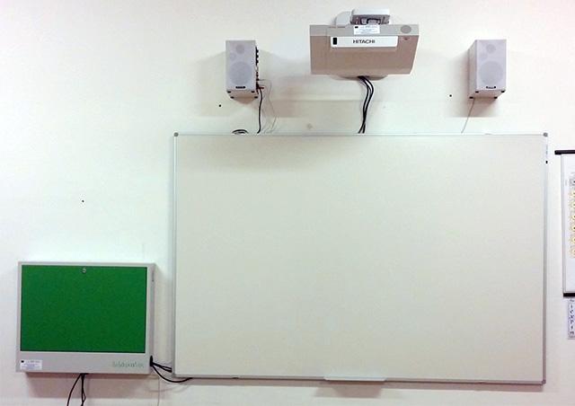 Foto di un videoproiettore con altoparlanti, lavagna, notebook e armadietto porta notebook installato nelle aule